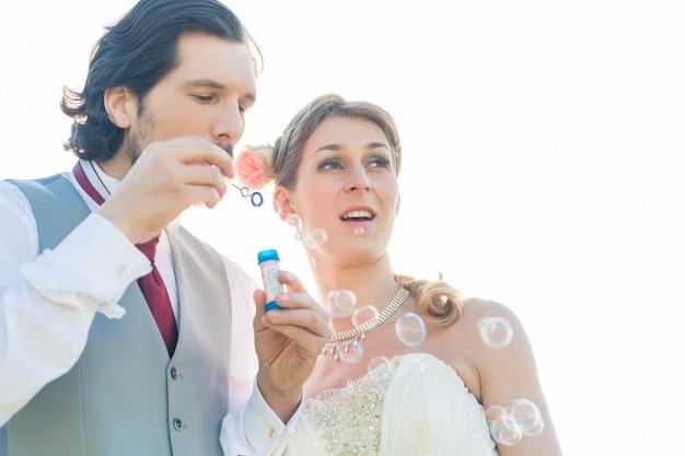 Ślub para dmuchanie baniek mydlanych na zewnątrz