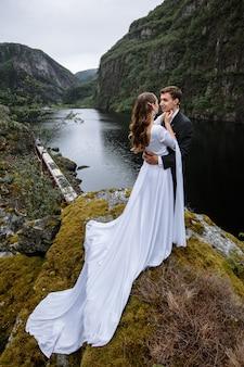 Ślub para stojący na skale, na tle rzeki