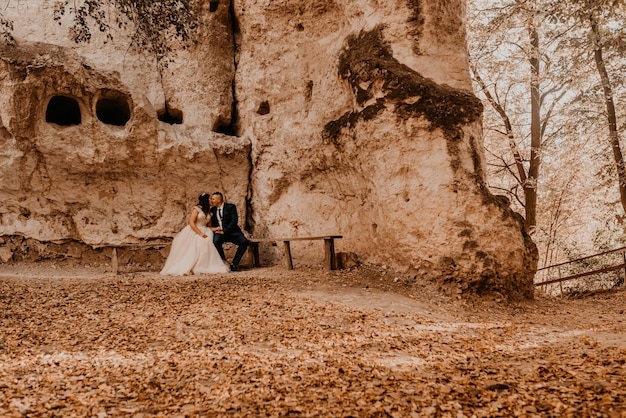 Ślub para zakochanych mężczyzna i kobieta siedzi na ławce pod skalnym klasztorem bakota w lesie jesienią