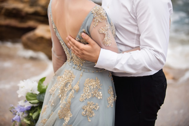 Ślub. ślub nad morzem. para zakochanych po ślubnym spacerze na morzu. pan młody obejmuje piękną pannę młodą w eleganckiej niebieskiej sukni ślubnej i trzyma haft ręczny, pokazując ich uczucia i miłość