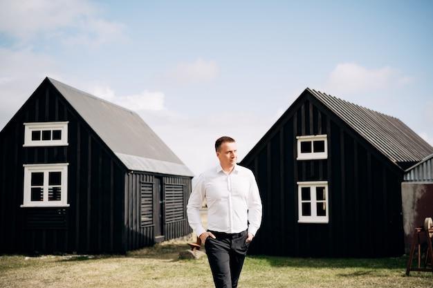 Ślub w destynacji islandzki mężczyzna w białej koszuli spaceruje między dwoma drewnianymi czarnymi domami