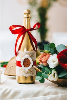 Ślubna butelka szampana pomalowana na złoto jest ozdobiona rustykalnym stylem, owinięta białą koronką i czerwoną wstążką.