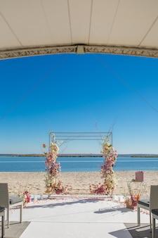 Ślubna chuppa nad brzegiem rzeki ozdobiona świeżymi kwiatami