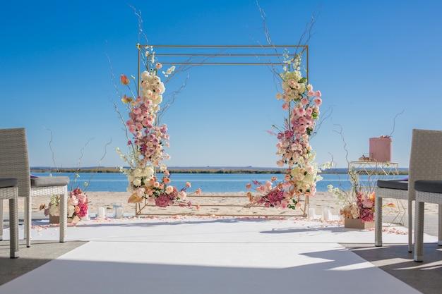 Ślubna chuppa nad brzegiem rzeki ozdobiona świeżymi kwiatami.
