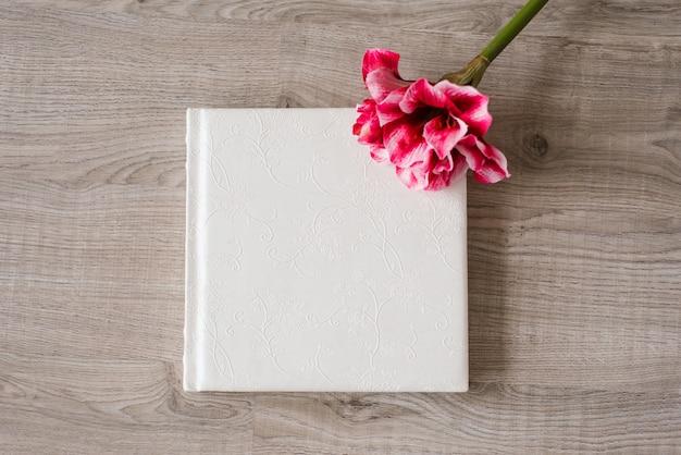 Ślubna fotoksiążka w koronkowej skórzanej oprawie na beżowym tle i obok niej jasny różowy kwiat