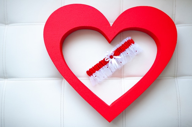 Ślubna panna młoda podwiązka wśrodku czerwonej kierowej kształt formy