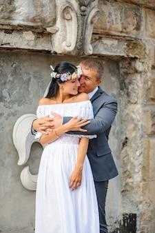 Ślubna sesja zdjęciowa na tle starego budynku. państwo młodzi delikatnie się przytulają.