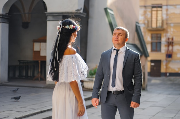 Ślubna sesja zdjęciowa na tle starego miasta. państwo młodzi patrzą na siebie. skoncentruj się na człowieku.