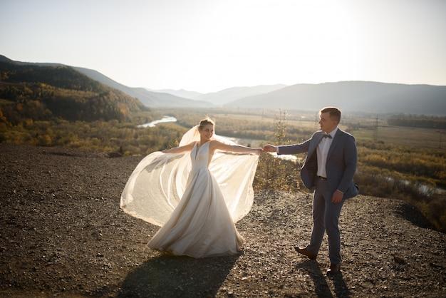 Ślubna sesja zdjęciowa pary młodej w górach. sesja zdjęciowa o zachodzie słońca.