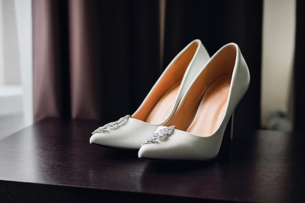 Ślubne białe buty panny młodej ze srebrnymi kolczykami
