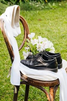 Ślubne czarne buty i białe szpilki z bukietem kwiatów na drewnianym krześle w ogrodzie