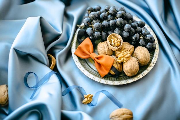 Ślubne dekoracje z winogronami i dokrętkami w półkowym bocznym widoku talerzu na błękitnym sukiennym tle