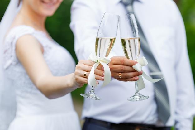 Ślubne kieliszki w rękach nowożeńców
