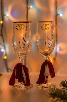 Ślubne okulary na tle świecącej girlandy świątecznej w kolorze pomarańczowym.