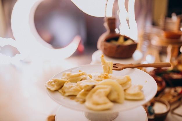 Ślubne stoły z jedzeniem w restauracji z dekoracjami