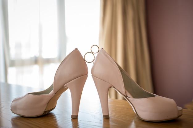 Ślubne złote obrączki między różowymi butami panny młodej. ceremonia