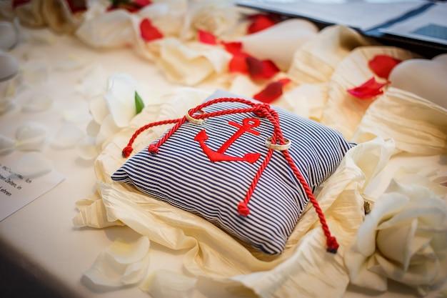 Ślubne złote obrączki wraz z czerwonym sznurem na poduszce w paski z kotwicą. ceremonia zaślubin
