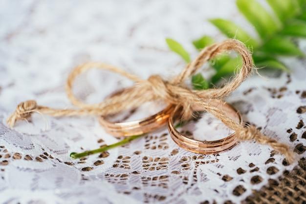 Ślubne złote pierścienie związane sznurkiem na rustykalnym tle konopie i koronki.
