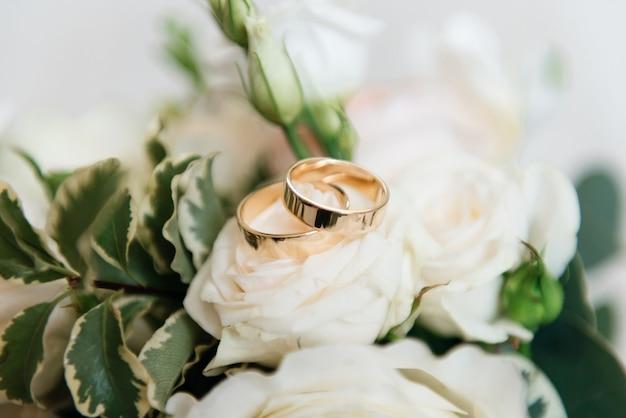Ślubni pierścionki zaręczynowi i kwiaty poślubiają bukieta tło, selekcyjna ostrość, makro-