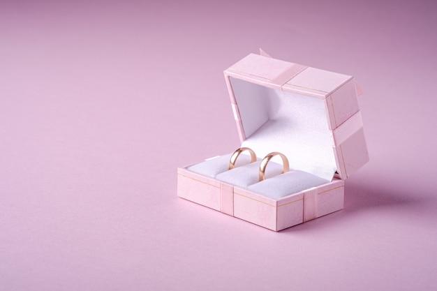 Ślubni złociści pierścionki w różowym prezenta pudełku na miękkiej części różowym tle, kąta widok, kopii przestrzeń