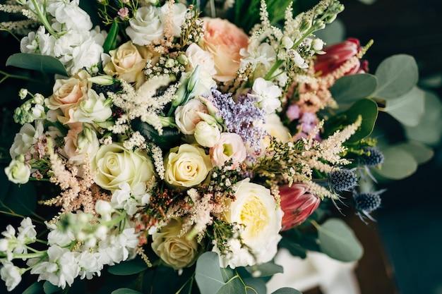 Ślubny bukiet białych i kremowych róż, gałęzi eukaliptusa protea eryngium i delphinium