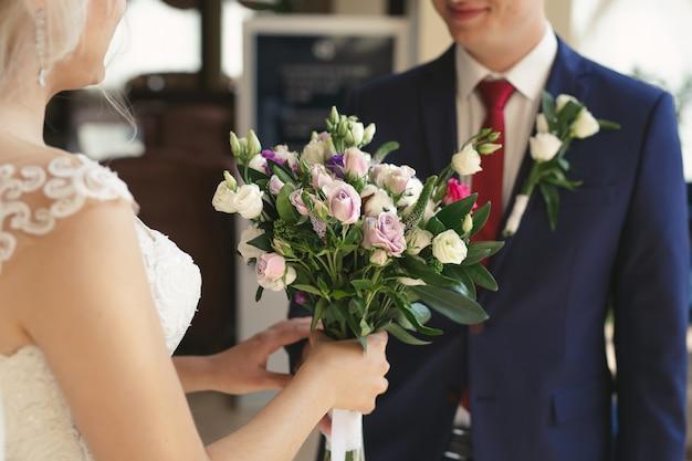 Ślubny bukiet białych i liliowych kwiatów w rękach panny młodej