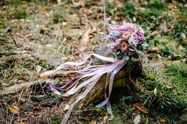 Ślubny bukiet ślubny z kwiatami zdobionymi wstążkami na zielonej trawie.