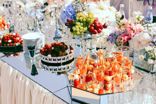 Ślubny catering z owocami i przekąskami na ozdobionym stole