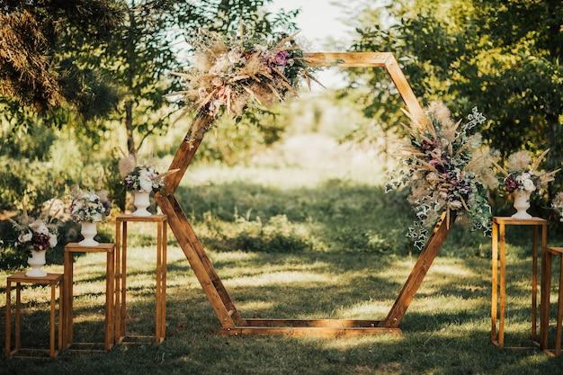 Ślubny drewniany łuk w stylu rustykalnym ozdobiony trawą i kwiatami w kolorze pola siana.