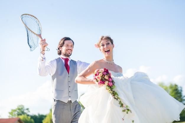 Ślubny pan młody łapie panny młodej z siecią