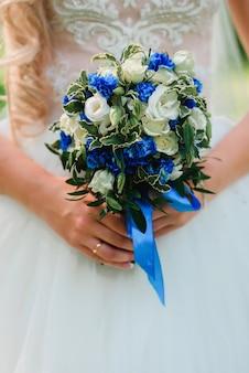 Ślubny piękny bukiet z białych róż i niebieskich kwiatów w rękach panny młodej z pierścieniem