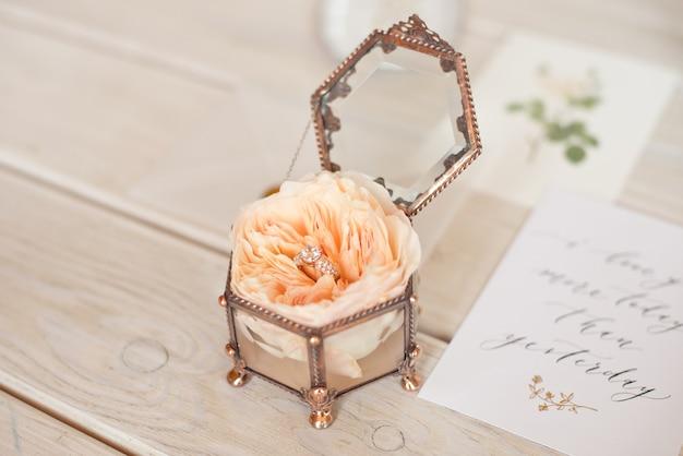 Ślubny stojak na szkatułkę z kwadratową szkatułką z różą piwonii i kartą z zaproszeniem do obrączki.