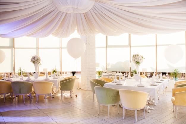 Ślubny wystrój, weselne stoły w restauracji z białymi kwiatami i ogromnymi białymi balonami