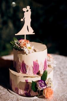 Ślubny wystrój z ciastem na drewnianej ławce na tle wodospadu