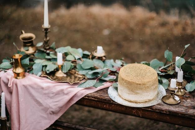 Ślubny wystrój ze złotym tortem na drewnianej ławce na tle wodospadu
