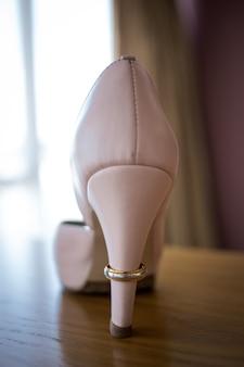 Ślubny złoty pierścionek na pięcie różowego buta panny młodej. ceremonia