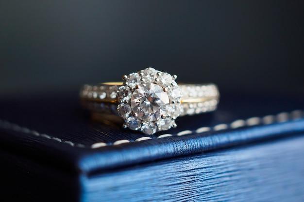 Ślubny złoty pierścionek z brylantem na pudełku z biżuterią