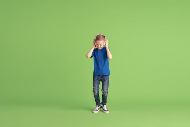 Słucha muzyka szczęśliwy chłopiec bawi się i ma zabawę na zielonej ścianie. dziecko rasy kaukaskiej w jasnych kolorach wygląda zabawnie, śmiejąc się, uśmiechając. pojęcie edukacji, dzieciństwa, emocji, wyrazu twarzy.