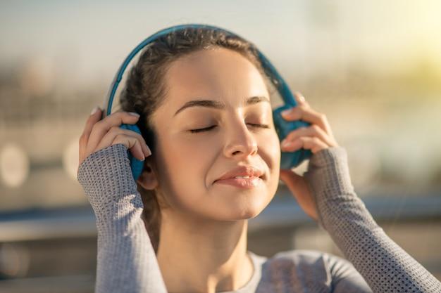 Słuchać muzyki. zdjęcie przedstawiające dziewczynę w słuchawkach, która wygląda na zadowoloną. waist