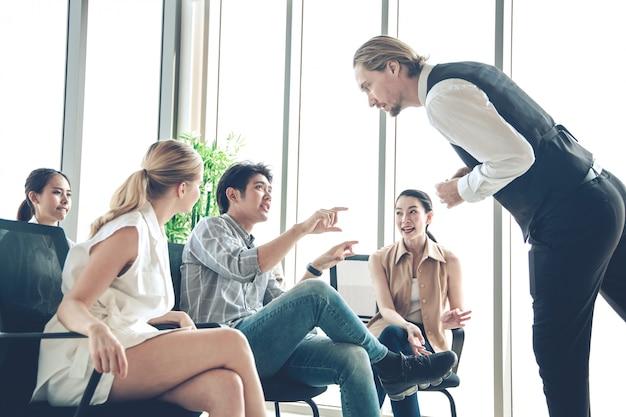 Słuchacze zadają pytania podczas spotkania w biurze.