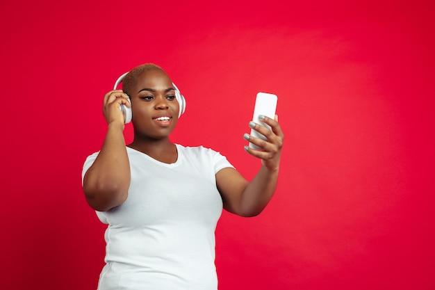 Słuchaj muzyki, graj. portret młodej kobiety afroamerykańskiej na czerwono