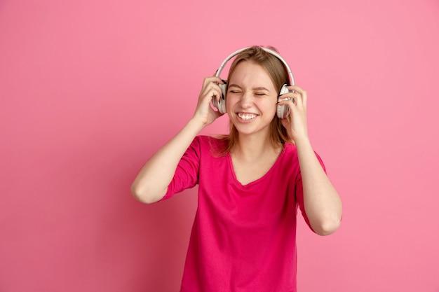 Słuchaj muzyki, szczęśliwy. kaukaski portret młodej kobiety na białym tle na różowej ścianie, monochromatyczne. piękna modelka.