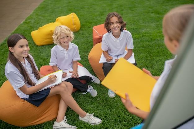 Słuchający. dzieci w wieku szkolnym siedzą razem i słuchają kolegi z klasy na flipcharcie