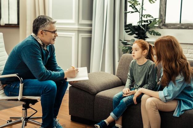 Słucham. miły profesjonalny psycholog patrzący na swoich pacjentów, będąc gotowym do pisania