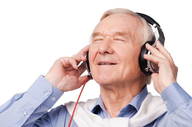 Słuchanie jego ulubionej muzyki. portret wesołego starszego mężczyzny w słuchawkach, słuchającego muzyki i trzymającego oczy zamknięte, stojąc na białym tle