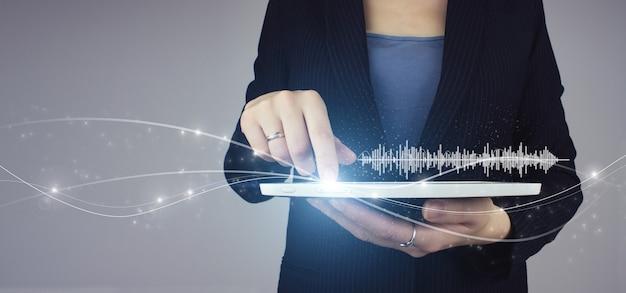 Słuchanie muzyki na urządzeniach mobilnych. rozpoznawanie głosu. biała tabletka w ręku bizneswoman z cyfrowym hologramem ścieżki dźwiękowej, fala ikona znak na szarym tle.