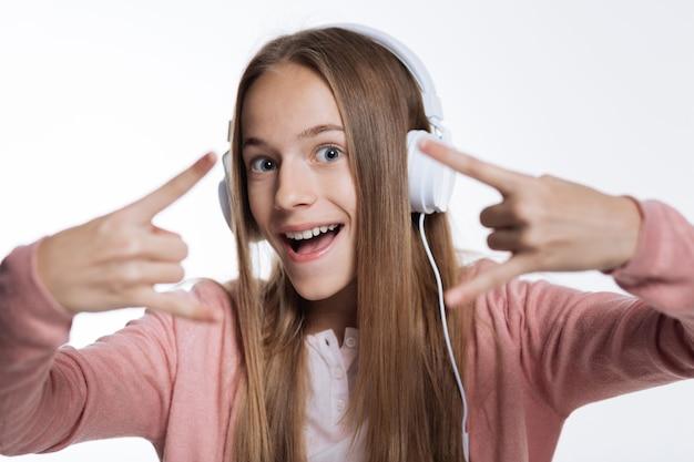 Słuchanie muzyki rockowej. pogodna nastolatka słuchająca muzyki w słuchawkach i pokazująca rogi obiema rękami, uśmiechając się radośnie