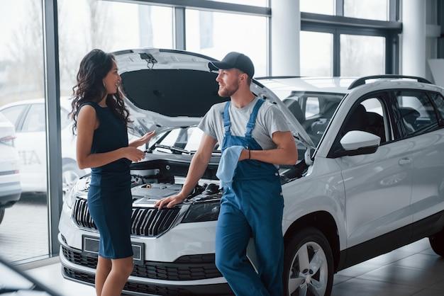 Słuchanie wyjaśnień. kobieta w salonie samochodowym z pracownikiem w niebieskim mundurze, odbierając naprawiony samochód