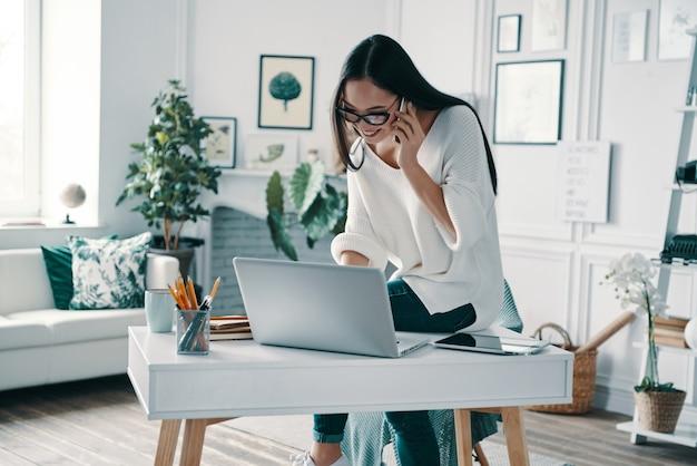 Słuchanie wymagań klientów. piękna młoda kobieta korzysta z laptopa i rozmawia przez telefon podczas pracy w domowym biurze