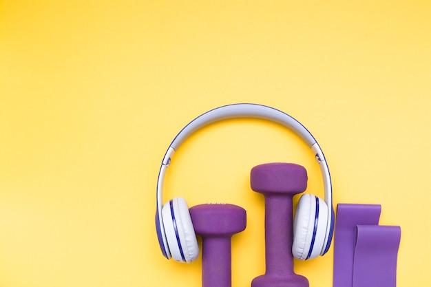 Słuchawki bezprzewodowe, gumka i fioletowe hantle na żółtym tle, miejsce na kopię, widok z góry